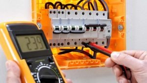 Electrician testing electrical equipment consumer unit